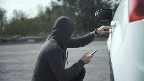 Ladrón adaptación coche usando el teléfono móvil almacen de metraje de vídeo