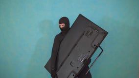 Ladrón alegre en una máscara del pasamontañas que robó la TV y mira feliz y que imitaba almacen de video