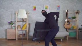Ladrón anónimo en una máscara del pasamontañas que roba la TV en la casa y que experimenta lesión del dolor de espalda almacen de metraje de vídeo