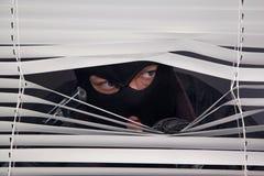 Ladrón con el arma que mira hacia fuera la ventana Imágenes de archivo libres de regalías