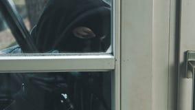 Ladrón con la puerta de la rotura de la palanca para entrar en la casa almacen de metraje de vídeo