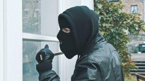 Ladrón con la puerta de la rotura de la palanca para entrar en la casa