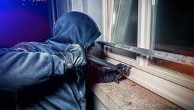 Ladrón con la puerta de la rotura de la palanca para entrar en la casa imágenes de archivo libres de regalías