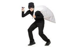 Ladrón con un bolso y linterna en manos Foto de archivo libre de regalías