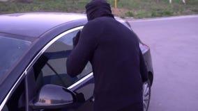 Ladrón con una palanca cerca de la puerta de coche almacen de video