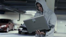 Ladrón de coches con el ordenador portátil en el estacionamiento subterráneo almacen de metraje de vídeo