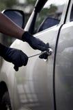 Ladrón de coches que usa una herramienta para romperse en un coche. Fotos de archivo libres de regalías
