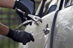 Ladrón de coches que usa una herramienta para romperse en un coche. Imagenes de archivo