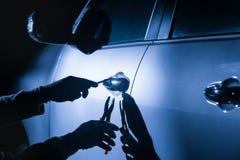 Ladrón de coches que usa una herramienta para romperse en un coche Fotos de archivo libres de regalías
