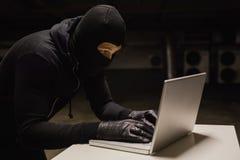 Ladrón en el escritorio que corta un ordenador portátil Fotografía de archivo