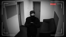 Ladrón en la máscara que corta la cámara de vigilancia en el edificio corporativo, criminal almacen de metraje de vídeo