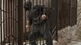 Ladrón en palo de la tenencia de la máscara y el sliping a través de la cerca almacen de metraje de vídeo