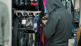 Ladrón en tienda, gángster que hace compras, ropa de ocultación del hombre en la tienda almacen de metraje de vídeo