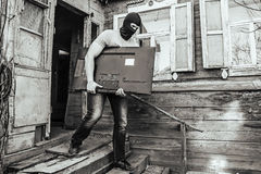 Ladrón en una máscara con túnica la casa Foto de archivo libre de regalías