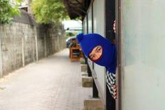 Ladrón enmascarado que oculta adentro detrás de la cartelera lista para confiar crimen foto de archivo