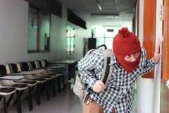 Ladrón enmascarado que se escapa después de escabullirse en la casa Concepto del crimen imagenes de archivo
