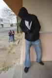 Ladrón Hiding Behind Wall que mira a muchachas imagenes de archivo