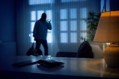 Ladrón o intruso dentro de una casa imagenes de archivo
