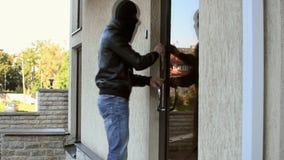 Ladrón que intenta abrir la puerta de la oficina almacen de video