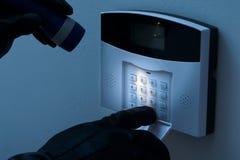 Ladrón que intenta desarmar el sistema de alarma de la seguridad Imagenes de archivo