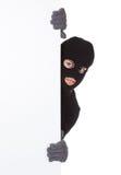 Ladrón que mira alrededor de una muestra en blanco Imagen de archivo libre de regalías