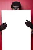 Ladrón que oculta detrás del anuncio Imagenes de archivo