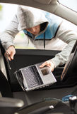 Ladrón que roba el ordenador portátil del coche Imagenes de archivo