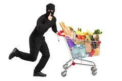 Ladrón que roba una carretilla de mano con los productos fotos de archivo