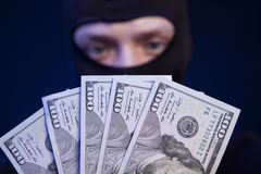 Ladrón que sostiene el dinero aislado en azul marino fotografía de archivo libre de regalías
