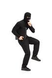 Ladrón que sostiene una cartera con el dedo en los labios Imagen de archivo