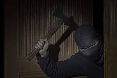 Ladr?n con un hacha en su mano y en un sombrero con una raja para los chivatos de los ojos en la casa a trav?s de la puerta en la imagen de archivo