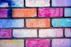 Ladrillos pintados al color del arco iris en brickwall Brickwall como ejemplo del arte de los niños Fotografía de archivo libre de regalías
