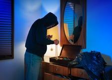 Ladrón casero encapuchado que toma la joyería Imagen de archivo libre de regalías