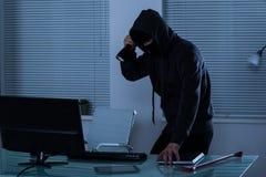 Ladrón con la linterna en oficina Foto de archivo libre de regalías