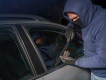 Ladrón encapuchado que mira para romperse en un coche Fotografía de archivo