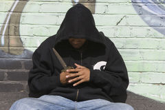 Ladrón que lleva la chaqueta negra que sostiene un cuchillo Foto de archivo libre de regalías