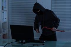 Ladrón que roba la computadora portátil Foto de archivo libre de regalías