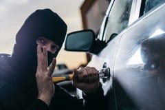 Ladro automatico in passamontagna nera che prova a rompersi nell'automobile fotografie stock libere da diritti