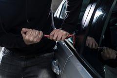 Ladro automatico in passamontagna nera che prova a rompersi nell'automobile fotografie stock
