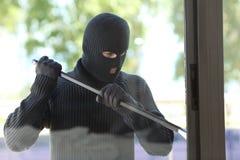 Ladro che prova ad aprire una finestra della casa immagine stock