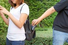 Ladro che prova a rubare il portafoglio nello zaino ed a allontanarsi w Fotografia Stock Libera da Diritti
