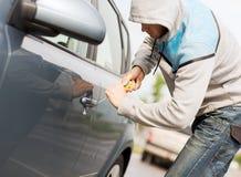 Ladro che rompe la serratura dell'automobile Immagini Stock Libere da Diritti