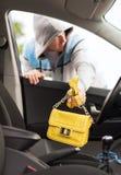 Ladro che ruba borsa dall'automobile Immagini Stock Libere da Diritti