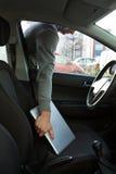 Ladro che ruba computer portatile attraverso la finestra di automobile Fotografia Stock