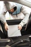 Ladro che ruba computer portatile dall'automobile Fotografia Stock