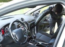Ladro che ruba un'automobile Immagine Stock