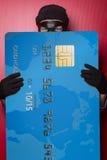 Ladro che si nasconde dietro la grande carta di credito blu Fotografie Stock