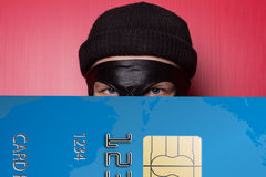 Ladro che sorride con la grande carta di credito blu Immagini Stock Libere da Diritti