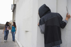 Ladrão com a faca que esconde atrás de canto e que espera duas meninas Imagens de Stock Royalty Free