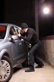 Ladrão com a máscara da extorsão que tenta roubar um carro Fotos de Stock Royalty Free